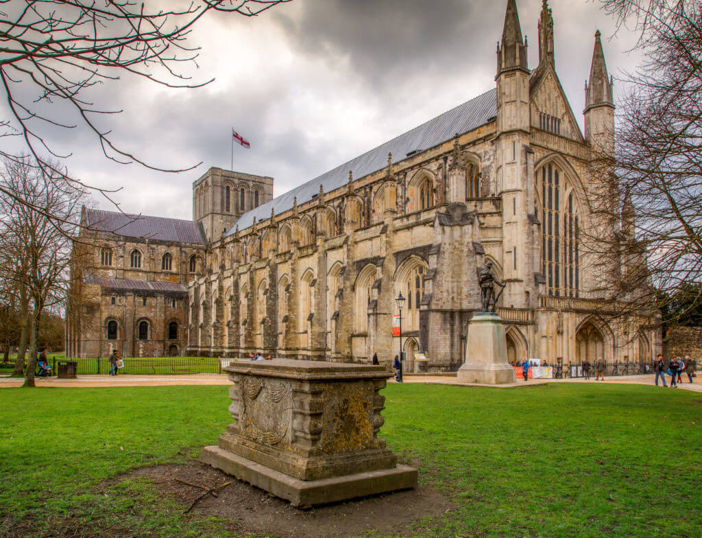 Winchester Cathedral with dramatic clouds and tomb in the foreground