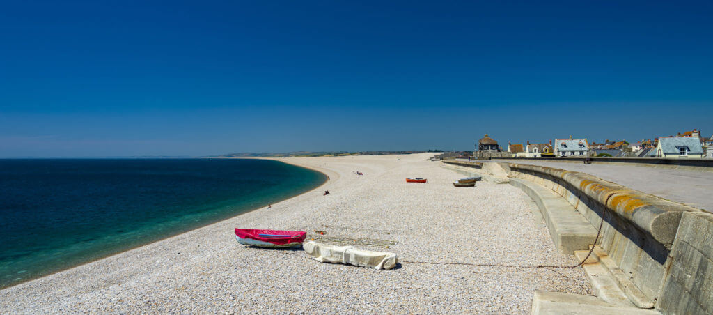 Boats moored on Chesil Cove beach in the Isle Of Portland Dorset