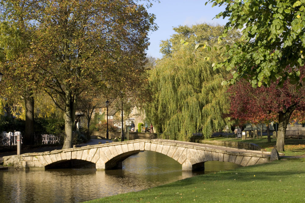 England, Gloucestershire, Cotswolds, Bourton on the Water, River Windrush, autumn colour, autumn sunshine