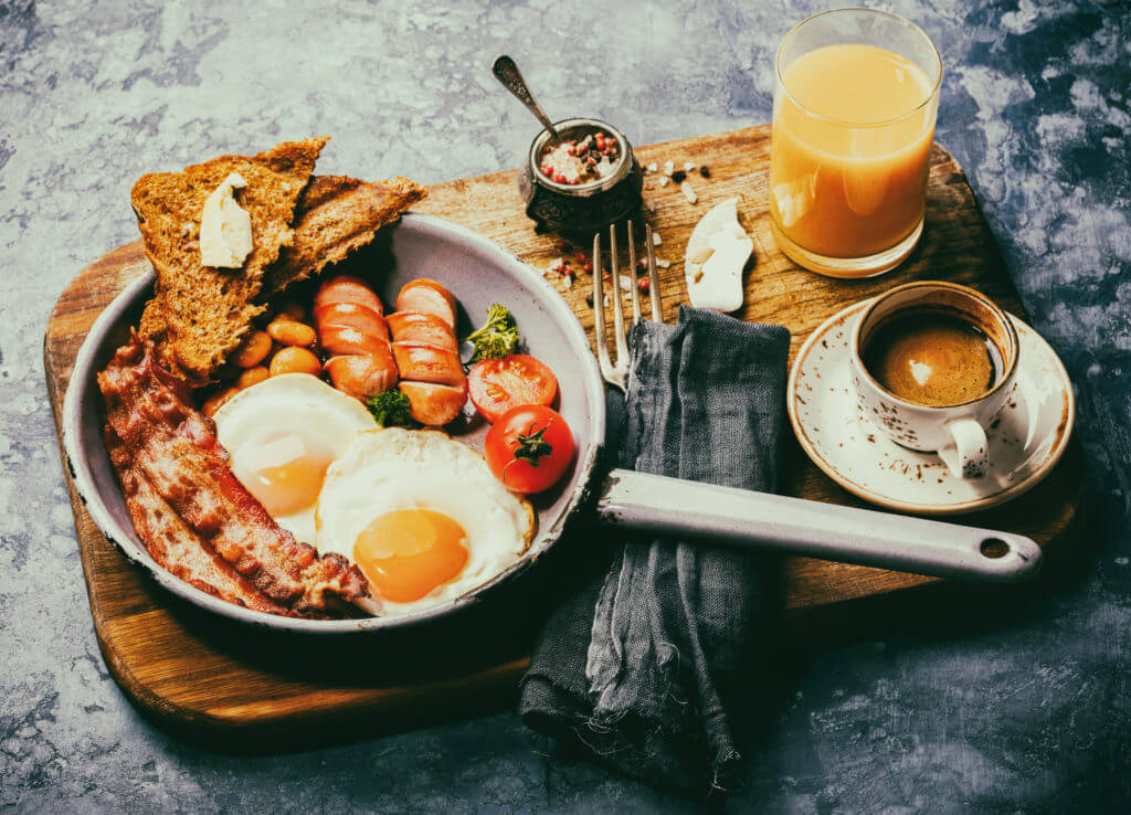 Traditional English Breakfast in the Frying Pan  Food on the Blue Background. Eggs, Sausages, Bacon, Beans,Toasts,Coffe and Orange juice Toned image Vintage style