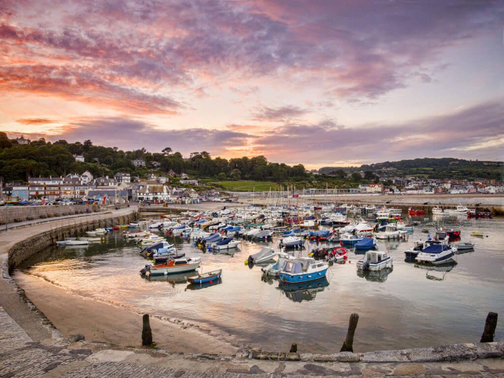 Lyme Regis, Dorset, England UK - The historic harbour on a summer evening.