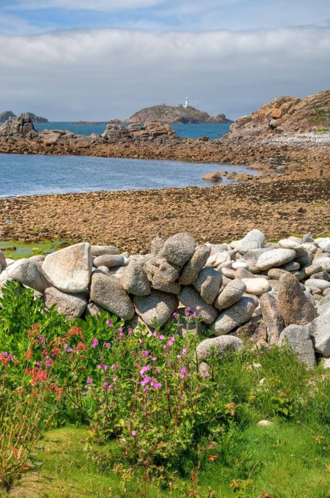 Looking over a dry-stone wall towards Round Island Lighthouse, St Martin's, Isles of Scilly, Cornwall, England.