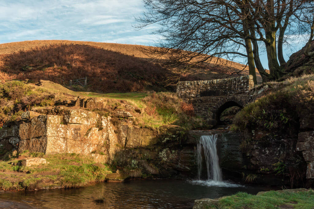 A waterfall and packhorse stone bridge at Three Shires Head in the Peak District National Park.